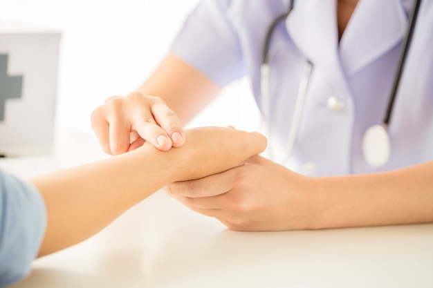 El doctor está comprobando el pulso de la paciencia con los dedos.