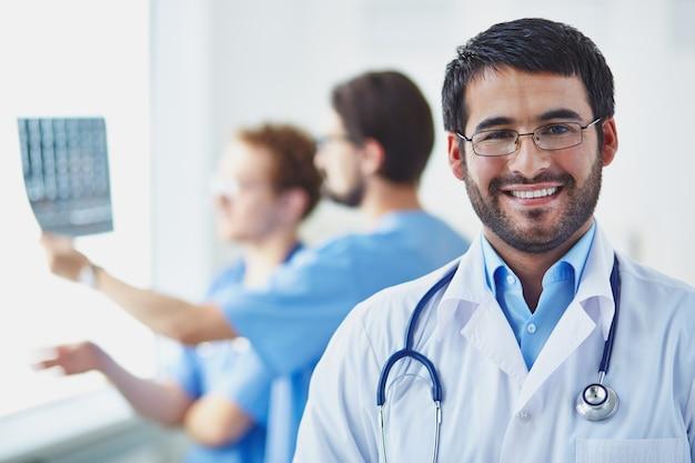 Doctor con compañeros de trabajo analizando una radiografía