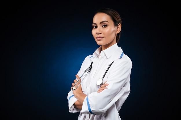Doctor confiado joven de la señora en la bata médica que mira
