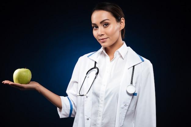 Doctor confiado joven de la señora que sostiene la manzana y que mira