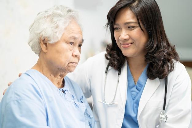 Doctor conmovedor paciente mujer asiática senior con amor.