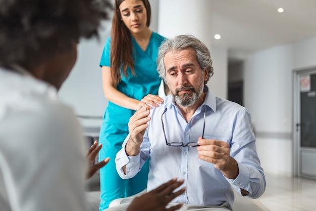 Doctor consolando al hombre molesto en la sala de espera del hospital paciente que recibe malas noticias que está desesperado y llorando