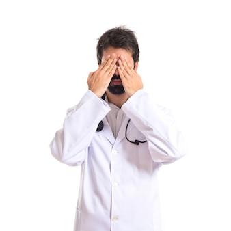 Doctor cubriendo sus ojos sobre fondo blanco aislado