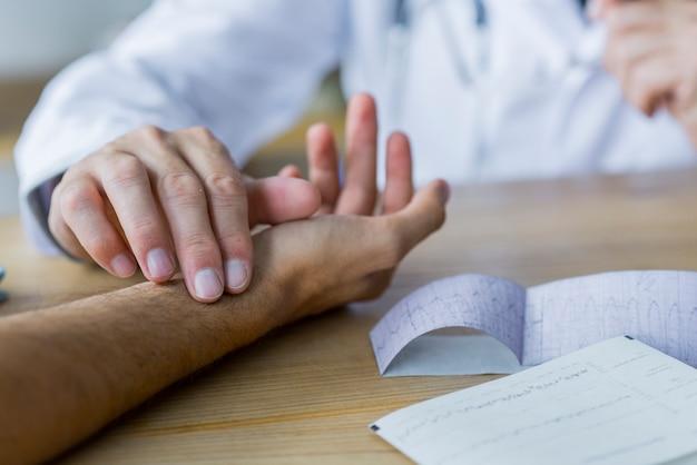 Doctor de cultivo que controla el pulso del paciente