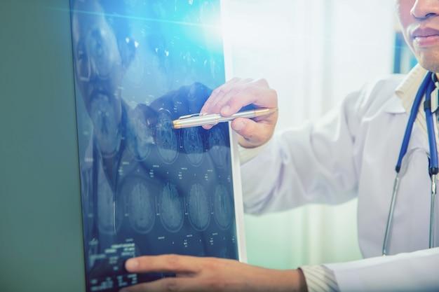 El doctor le da consejos al paciente sobre las exploraciones de resonancia magnética (rayos x) del cerebro