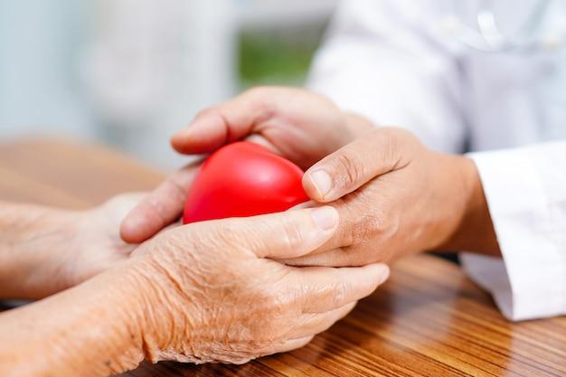 El doctor da el corazón rojo al paciente asiático mayor de la mujer.