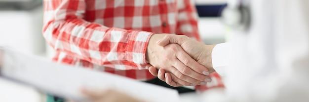El doctor se da la mano con el paciente y sostiene documentos concepto de seguro médico