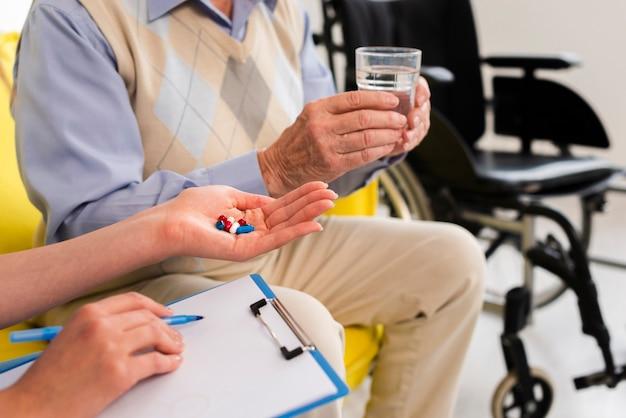 Doctor dando a un anciano sus pastillas