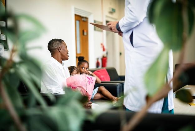Doctor dando buenas noticias a familiares en la sala de espera.