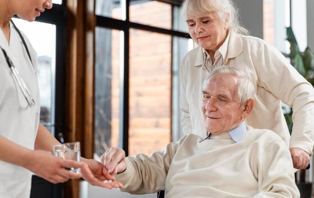Doctor dando pastillas a su paciente
