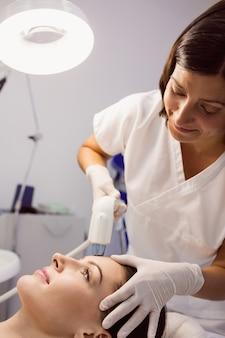 Doctor dando tratamiento cosmético a paciente femenino