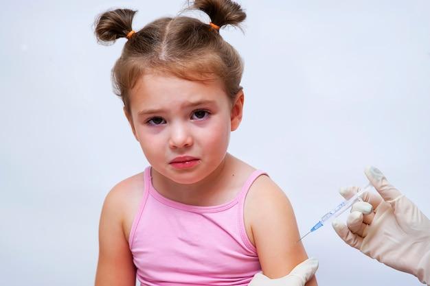 Doctor dando una vacuna inyectable a una niña.