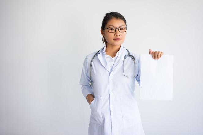 Doctor de sexo femenino asiático joven serio que muestra la hoja de papel en blanco.