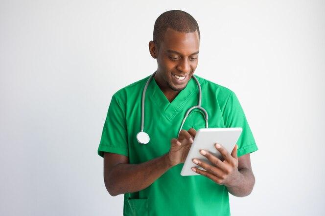 Doctor de sexo masculino negro sonriente que usa la tableta. tecnología en concepto de la medicina.