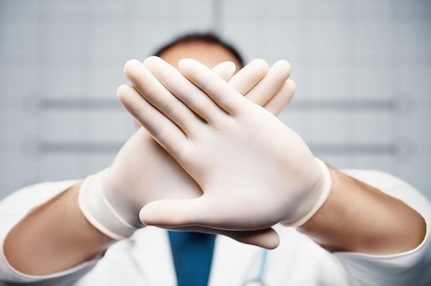 Doctor deja de hacer señales de prohibición doctor sosteniendo las manos cruzadas en guantes