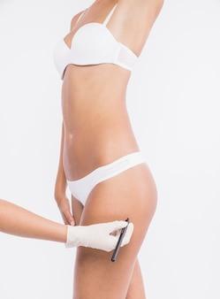 Doctor dibujando líneas en la cadera de la mujer
