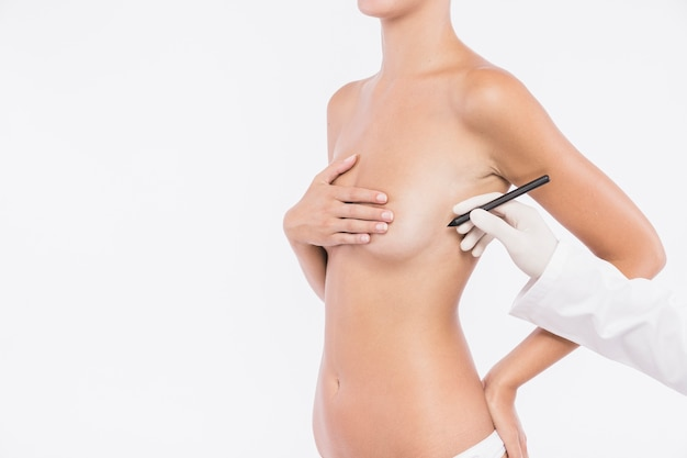 Doctor dibujando líneas en el cuerpo de la mujer