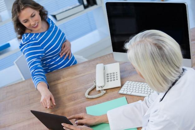 Doctor discutiendo con paciente embarazada sobre tableta digital