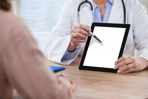Doctor discutiendo con el paciente sobre tableta digital en el hospital
