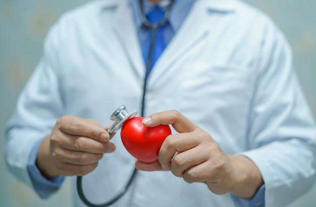 Doctor elegante asiático del hombre que lleva a cabo un corazón rojo