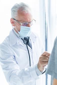 Doctor en máscara que examina el paciente de cosecha