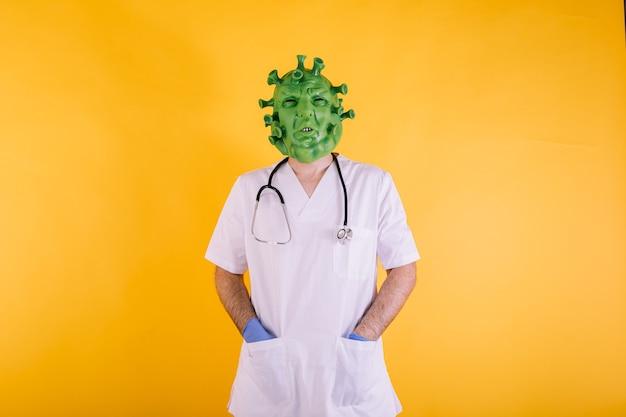 Doctor enfermera disfrazado de coronavirus con máscara de látex virus covid con las manos en los bolsillos sobre fondo amarillo concepto de coronavirus