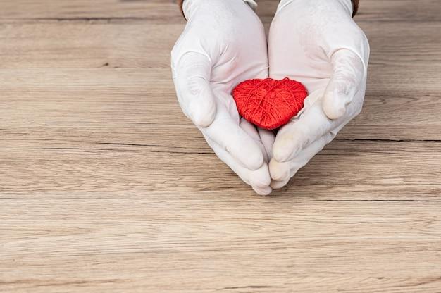 El doctor envolvió su mano alrededor del corazón rojo en el escritorio.