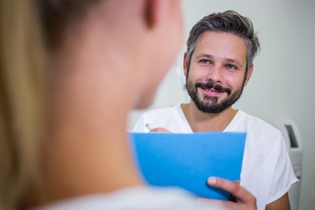 Doctor escribiendo en informes mientras discute con el paciente