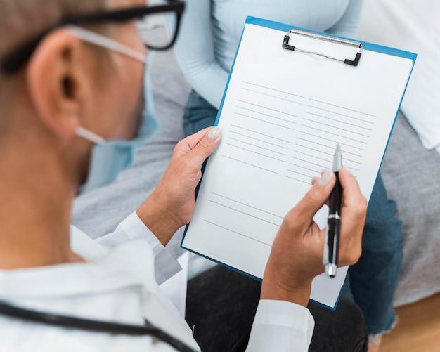 Doctor escribiendo notas en un portapapeles