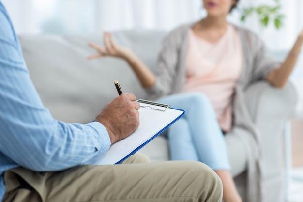 Doctor escribiendo en el portapapeles mientras consulta a una mujer embarazada en su casa
