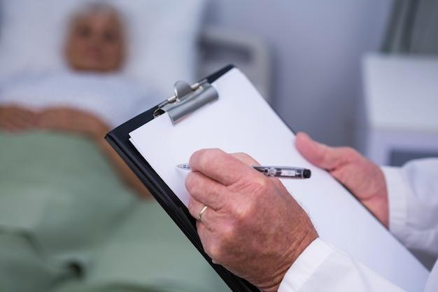 Doctor escribiendo en el portapapeles