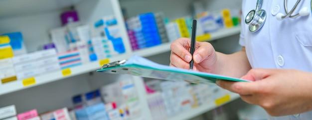 Doctor escribiendo prescripción con muchos medicamentos en estantes.