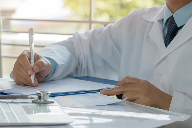 Doctor escribiendo prescripción portapapeles