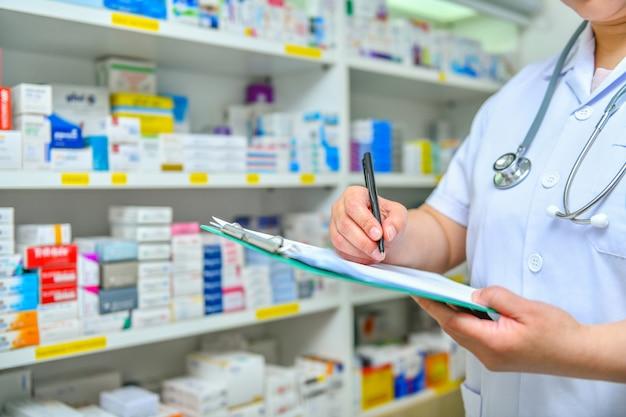 Doctor escribiendo recetas con muchos medicamentos en los estantes