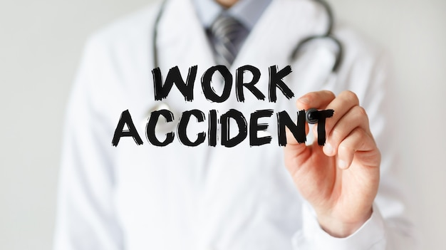 Doctor escrito palabra accidente laboral con marcador, concepto médico