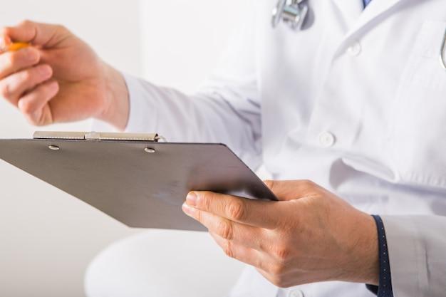 Doctor con el estetoscopio que escribe la prescripción de rx en el tablero en el fondo blanco, primer. servicio médico
