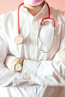 Doctor con un estetoscopio sobre fondo rosa