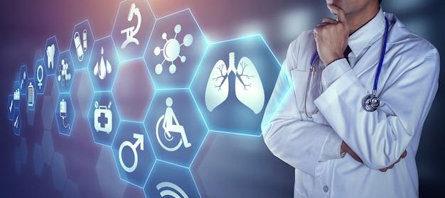 Doctor con estetoscopio tocando los iconos digitales