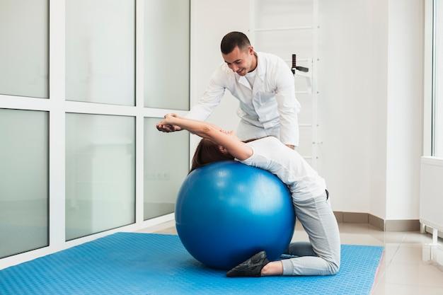 Doctor estirando paciente en pelota de ejercicios