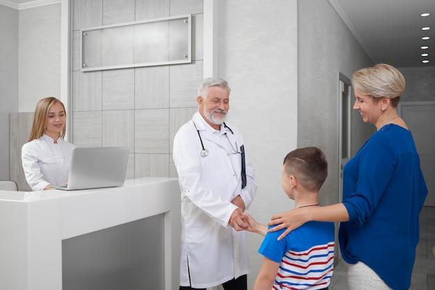 Doctor estrechándole la mano con el niño en consulta.
