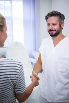 Doctor estrechándole la mano con paciente
