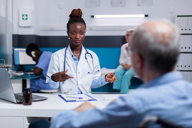 Doctor de etnia afroamericana hablando con anciano