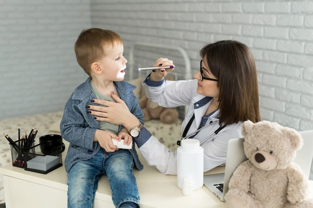 El doctor examina la garganta del niño