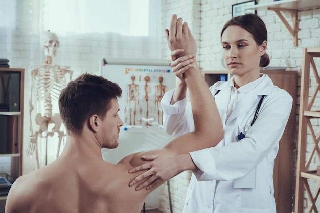 El doctor está examinando el brazo del atleta en hospital