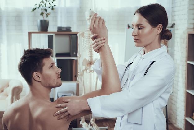 El doctor está examinando el brazo del atleta en el sitio de hospital