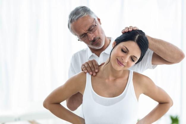 Doctor examinando y dando fisioterapia a una mujer embarazada