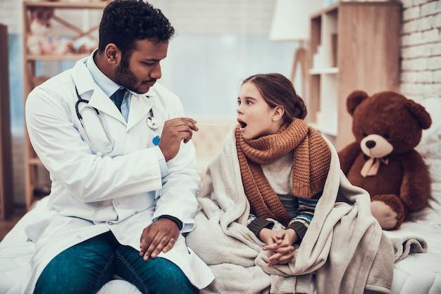 El doctor está examinando la garganta de la niña con frío.
