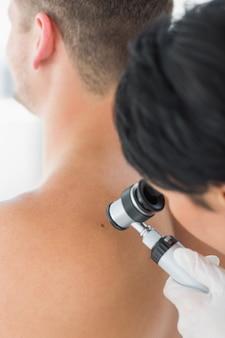 Doctor examinando melanoma en la parte posterior del hombre