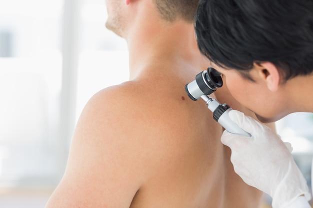 Doctor examinando mole en la parte posterior del hombre