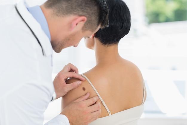 Doctor examinando mole en la parte posterior de la mujer